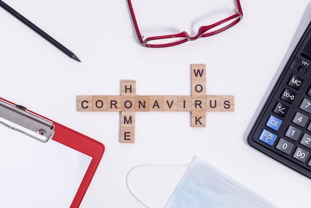 Text aus holzbuchstaben coronavirus arbeiten von zu hause aus. büromaterial, taschenrechner, tablet, brille, bleistift und medizinische schutzmaske auf dem desktop.