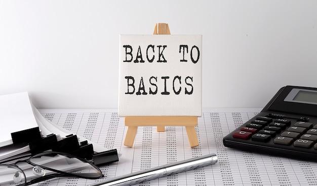 Text back to basics auf staffelei mit bürowerkzeugen und papier. ansicht von oben. unternehmen