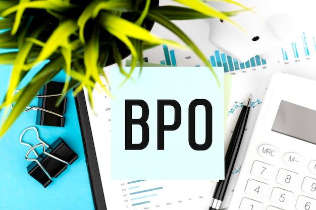Text bpo business process outsourcing auf blauem aufkleber, lupe, stift, grafiken. business-wohnung lag.