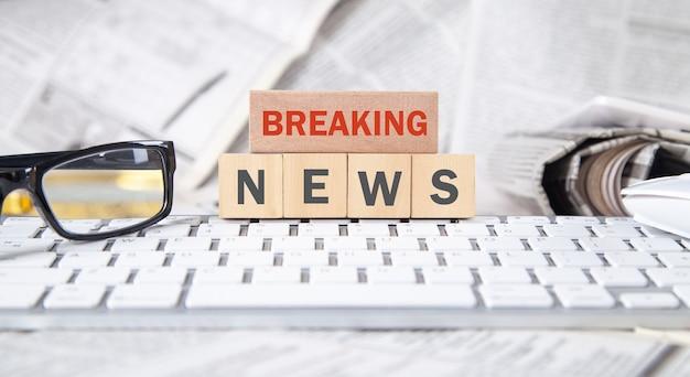 Text breaking news auf holzwürfel mit computertastatur, zeitungen und brillen.