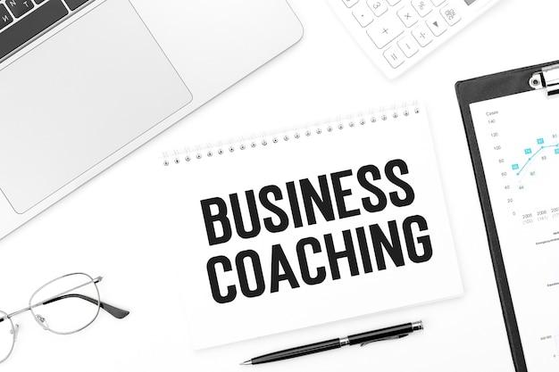 Text business coaching auf notebook, laptop, taschenrechner, stift, brille.