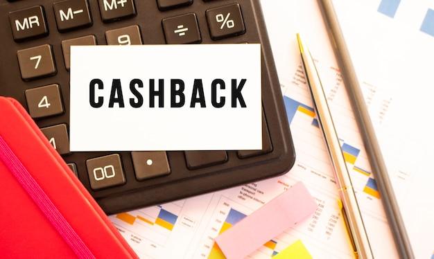 Text cashback auf weißer karte mit metallstift, taschenrechner und finanzdiagrammen