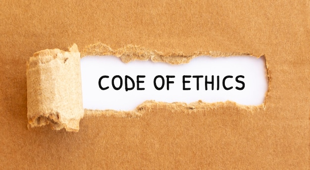 Text code of ethics erscheint hinter zerrissenem braunem papier, konzept