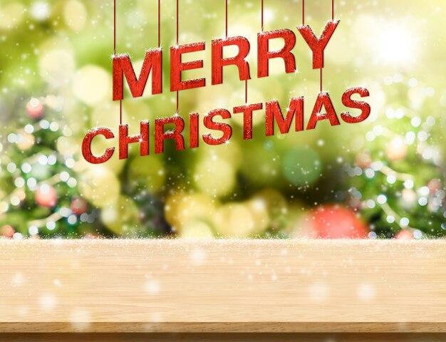 Text der frohen weihnachten, der über hölzerner tabelle hängt