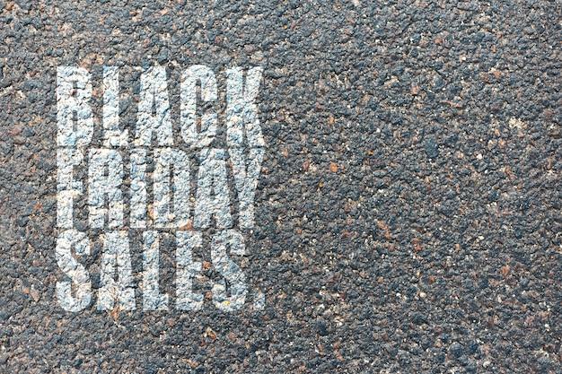 Text der schwarzen freitagverkäufe, auf dem hintergrund des asphalts.