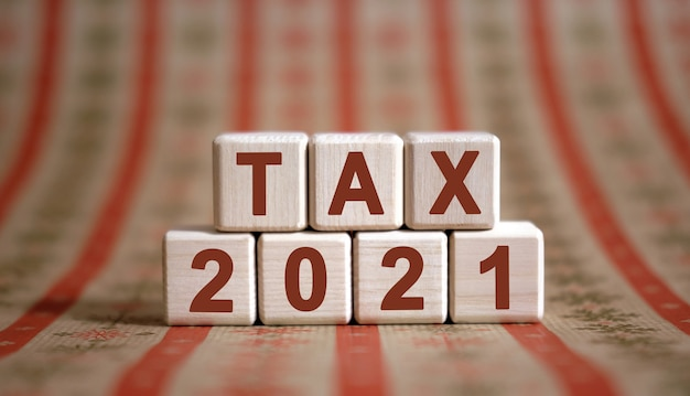 Text der steuer 2021 auf holzwürfeln auf einem monochromen hintergrund mit reflexion.