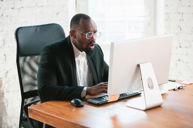 Text eingeben. afroamerikanischer unternehmer, geschäftsmann, der im büro konzentriert arbeitet. sieht ernst und beschäftigt aus, trägt klassischen anzug, jacke.