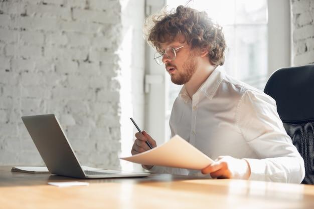 Text eingeben, analysieren, surfen. kaukasischer junger mann in geschäftskleidung, der im büro arbeitet. junge geschäftsfrau, managerin, die aufgaben mit smartphone, laptop, tablet erledigt, hat online-konferenz und studiert.