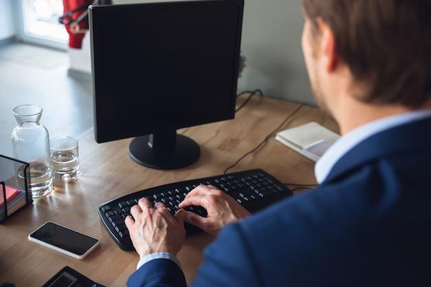 Text eingeben, arbeiten, aufmerksam antworten. junger mann, manager, der nach der quarantäne in sein büro zurückkehrt, fühlt sich glücklich und inspiriert. rückkehr ins normale leben. business, finanzen, emotionen konzept.