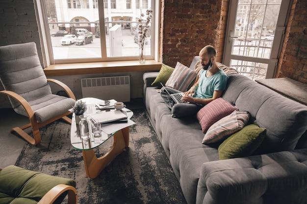 Text eingeben. junger mann, der zu hause yoga macht, während er unter quarantäne steht und freiberuflich online arbeitet