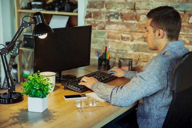 Text eingeben. mann, der während der quarantäne von coronavirus oder covid-19 von zu hause aus arbeitet, remote-office-konzept. junger geschäftsmann, manager, der aufgaben mit smartphone, computer erledigt, hat online-konferenz, treffen.