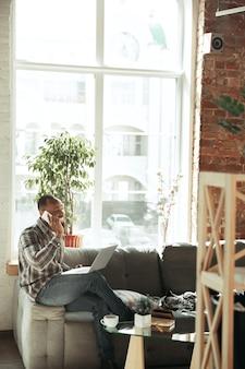 Text eingeben und telefonieren. mann, freiberufler während der arbeit im homeoffice während der quarantäne. junger geschäftsmann zu hause, selbst isoliert. verwenden von geräten. fernarbeit, prävention der ausbreitung von coronaviren.