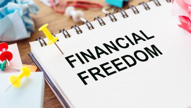 Text finanzielle freiheit auf briefpapier auf bürotisch