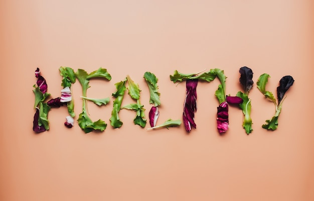 Text gesund mit grünen und lila salatblättern mischen auf beigem hintergrund. hochwertiges foto