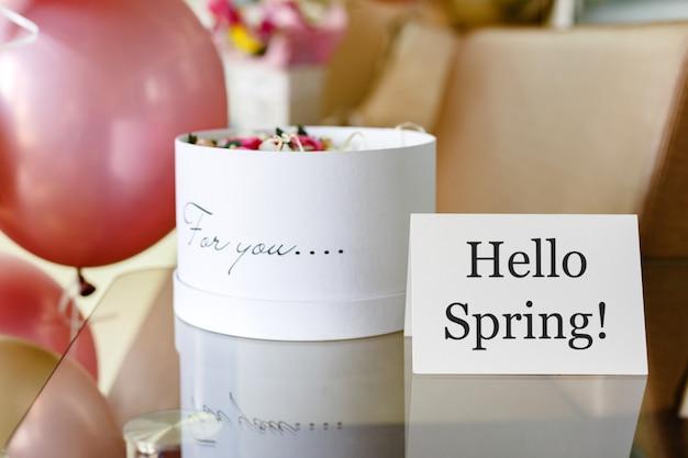Text hallo frühling auf weißer karte mit blumenkasten. runde schachtel des weißen hutes mit rosa rosenblumen