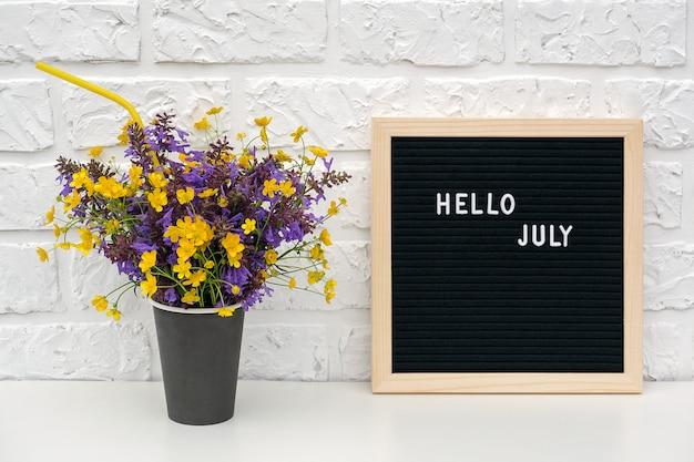 Text hallo juli auf schwarzem briefkasten und blumenstrauß von farbigen blumen