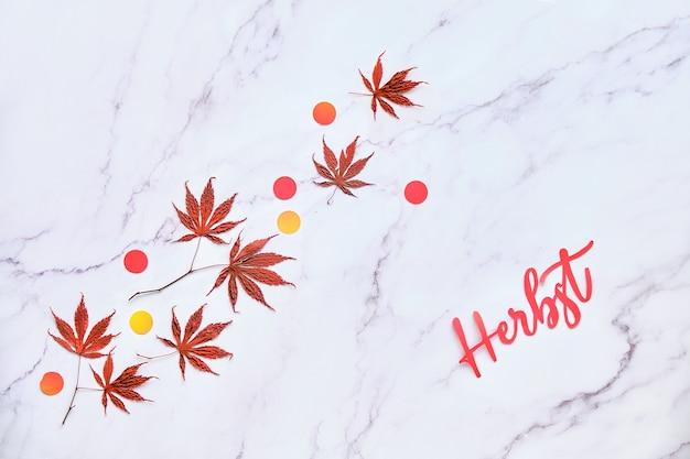 Text herbst bedeutet herbst in deutscher sprache. minimaler herbstlicher saisonaler hintergrund mit natürlichen ahornblättern und konfetti.