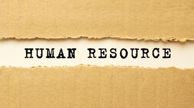 Text human resource erscheint hinter zerrissenem braunem papier. draufsicht.