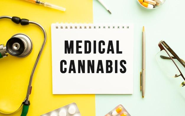 Text medizinisches cannabis auf notebook mit stethoskop und stift auf gelbem hintergrund.