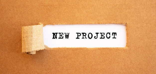 Text neues projekt erscheint hinter zerrissenem braunem papier