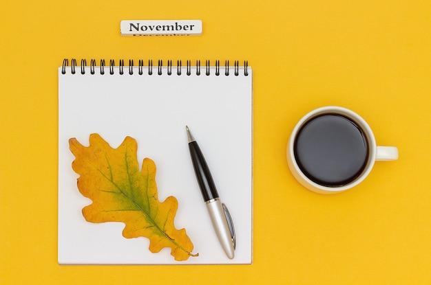 Text-november-kaffeetasse, offener notizblock mit stift und gelbes eichenblatt