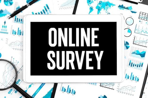Text online-umfrage auf dem tablet. stift, lupe und grafiken. unternehmenskonzept. flach liegen.