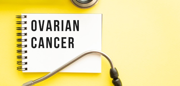 Text ovarian cancer auf notizbuch mit stethoskop auf gelber oberfläche