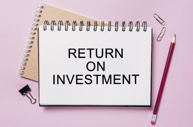 Text return on investment auf einem weißen aufkleber mit büropapieroberfläche