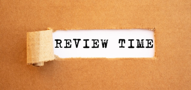 Text review time erscheint hinter zerrissenem braunem papier. für ihr design, konzept.