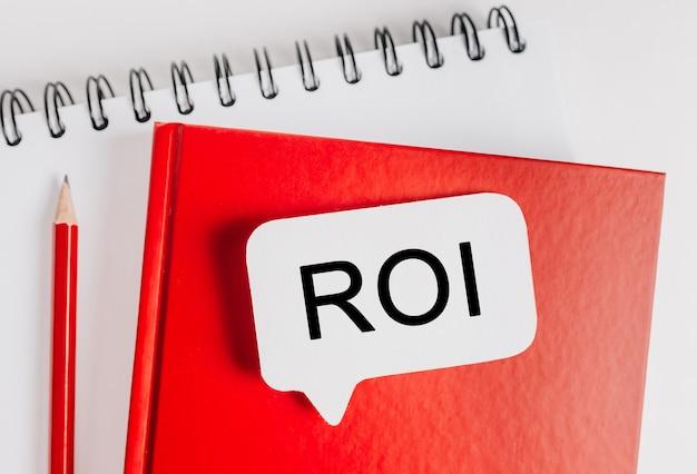 Text roi ein weißer aufkleber auf rotem notizblock mit büromaterial