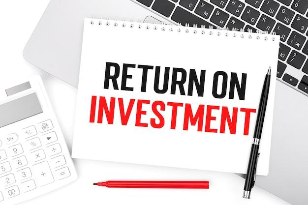 Text roi - return on investment auf notebook, laptop, taschenrechner, stift auf weißem hintergrund.