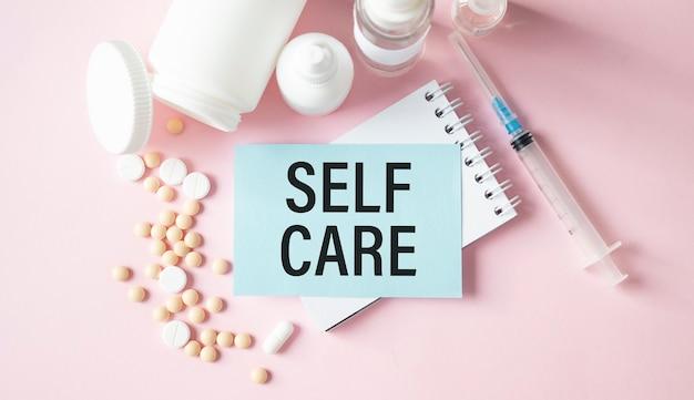 Text self care in der karte und pillen auf dem rosa