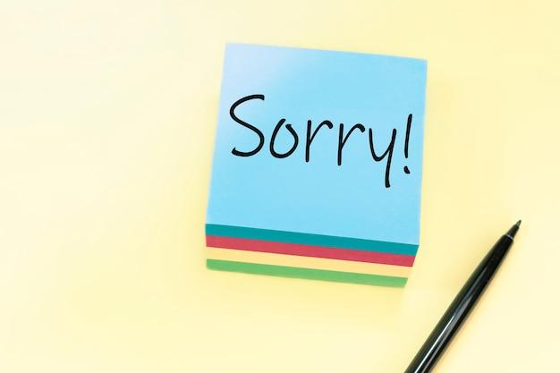 Text sorry handschriftlich mit schwarzem stift auf blauem aufkleber.