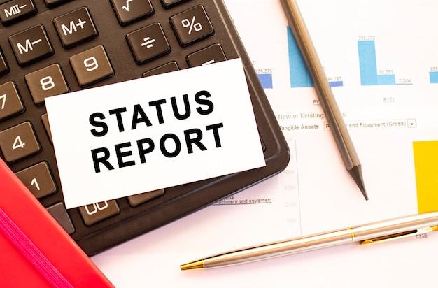 Text statusbericht auf weißer karte mit metallstift, taschenrechner und finanzdiagrammen. geschäfts- und finanzkonzept