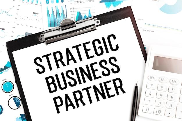 Text strategischer geschäftspartner auf zwischenablage, stift, taschenrechner, diagramme. unternehmenskonzept. flach liegen.