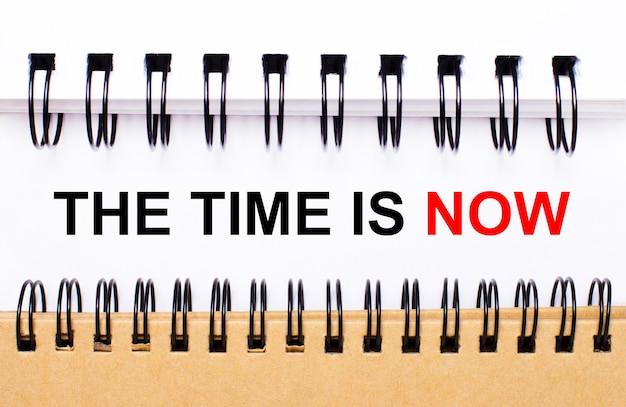 Text the time is now auf weißem papier zwischen weißen und braunen spiralnotizblöcken.