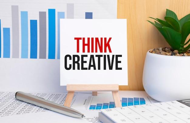 Text think creative auf staffelei mit office-tools und papier. ansicht von oben.