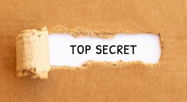 Text top secret erscheint hinter zerrissenem braunem papier, konzept