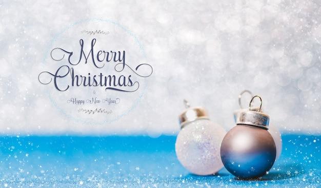 Text und ball der frohen weihnachten und des guten rutsch ins neue jahr auf klarem blauem funkelnboden