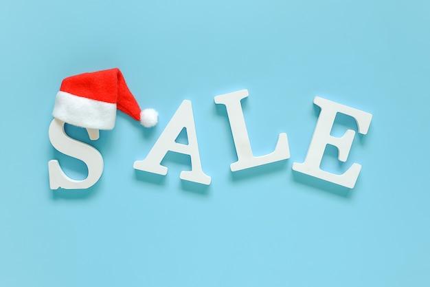 Text verkauf von weißen buchstaben und santa claus hut. konzept neujahr oder weihnachtsrabatt.