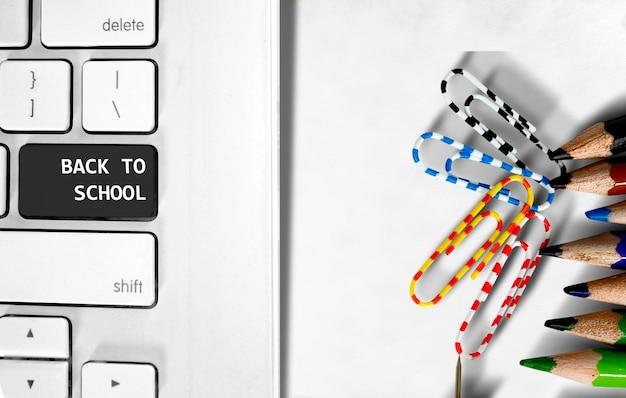 Text von zurück zur schule auf laptop-tastatur und buntstift auf dem schreibtisch. back to school-konzept