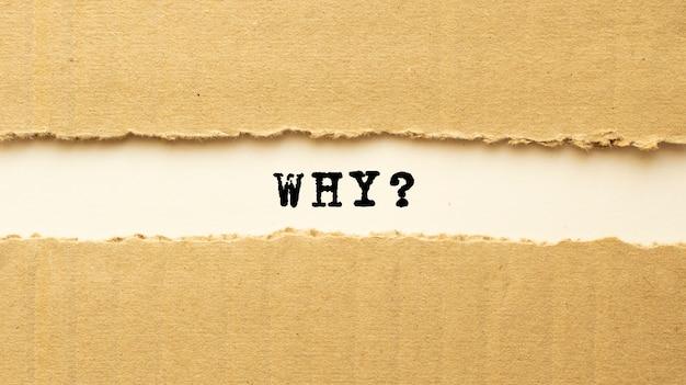 Text warum hinter zerrissenem braunem papier erscheinen. draufsicht.