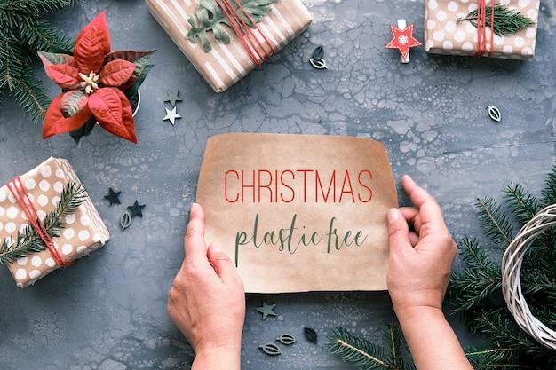 Text weihnachten plastik frei auf stück handwerk geschenkpapier in händen. flach lag auf grauem tisch mit weihnachtsgeschenken in handgeschöpftem braunem papier