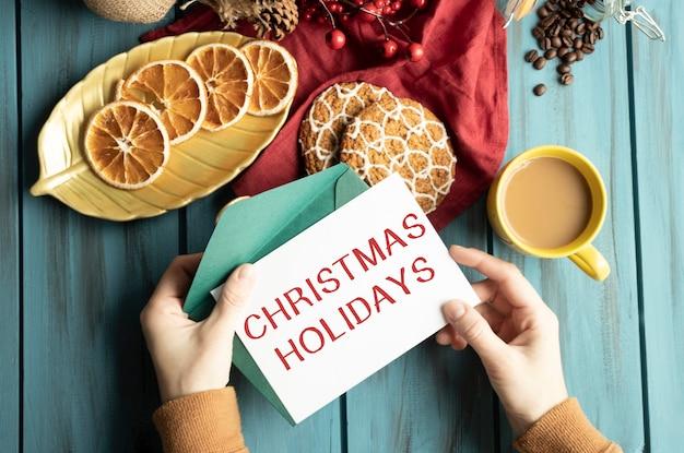 Text weihnachtsferien auf karte in der hand und tasse cappuccino auf einem weihnachtstisch verziert