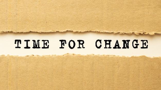 Text zeit für veränderung erscheint hinter zerrissenem braunem papier. ansicht von oben.
