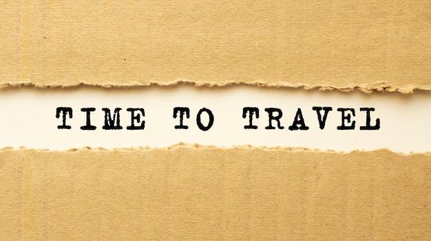 Text zeit zur reise erscheint hinter zerrissenem braunem papier. draufsicht.