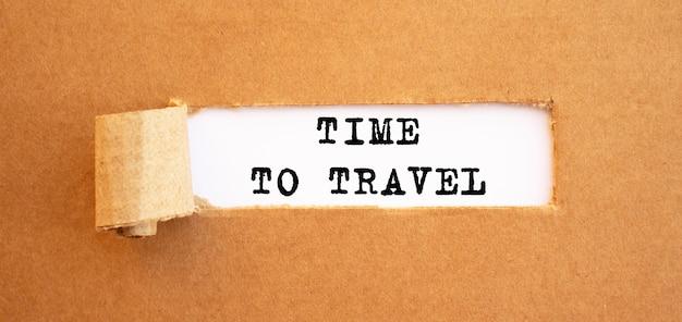 Text zeit zur reise erscheint hinter zerrissenem braunem papier für ihr designkonzept