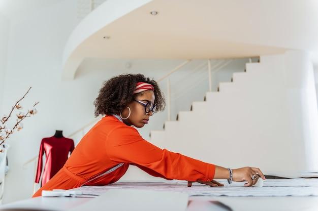 Textil kennzeichnen. konzentrierte gut aussehende näherin in rotem kostüm mit kreide als werkzeug für die arbeit