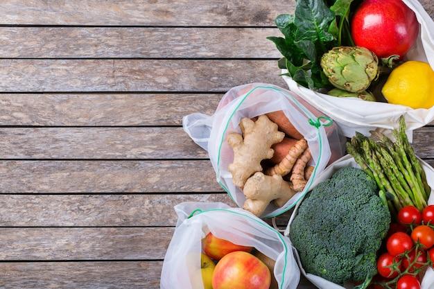 Textile netztasche mit produkten, obst und gemüse. zero waste, umweltfreundlich, plastikfrei recycelt, wiederverwendbar, nachhaltiges lebensmitteleinkaufskonzept. platz kopieren, flacher hintergrund