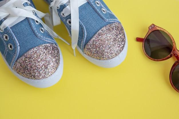 Textile spitzensneaker für kinder. mädchen schuhe an der gelben wand. mode kinderschuhe. smart lässige modische jeans und glänzende schuhe. sonnenbrillen und trendige kindersportschuhe. selektiver fokus